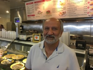 Owner Amir Movassat in front of the delicious grill section of the new Peachy's Market & Grill